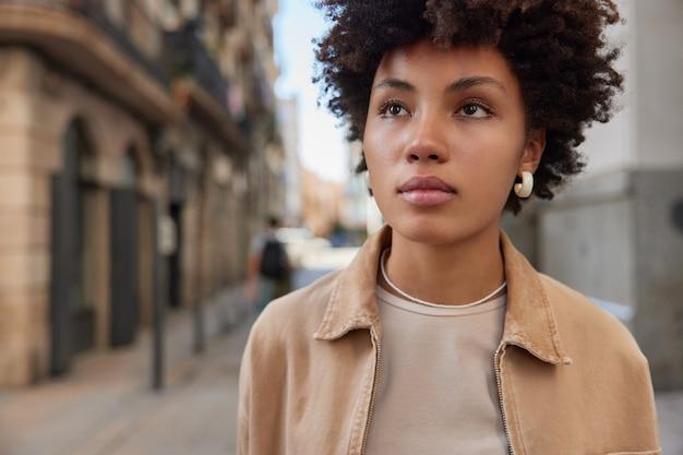 Женщина, одетая в повседневную одежду, гуляет по древнему городу, думает о будущем, с серьезным выражением лица смотрит вдаль