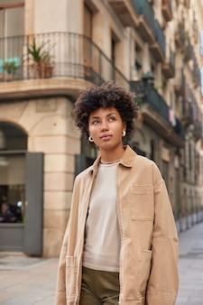 Женщина, одетая в повседневную одежду, гуляет по старинным зданиям в городе, мечтает о чем-то и думает, находит новые достопримечательности