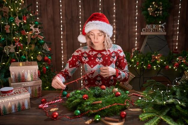 Женщина, одетая в новогодний дизайнерский свитер, делает венок ручной работы