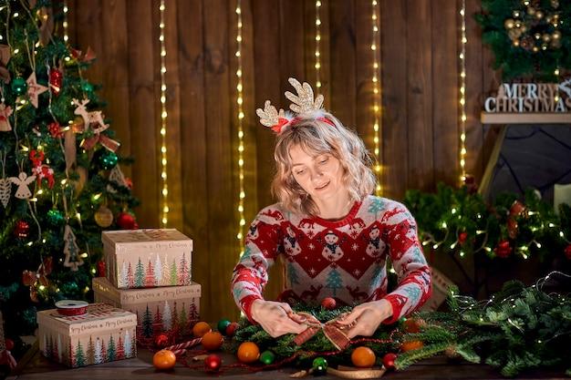 休日のテーブルに手作りのクリスマスリースを作るクリスマスセーターに身を包んだ女性。
