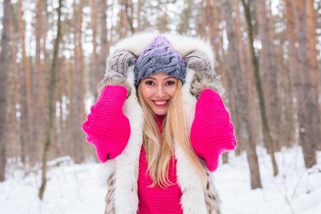 雪の自然の上に毛皮のチョッキを着た女性