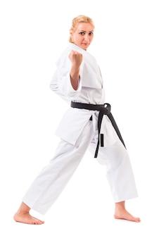 Женщина, одетая в кимоно с черным поясом и позирует в стойке для карате