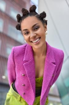 ピンクのジャケットを着た女性は前向きな感情を表現しますぼやけた背景に対して屋外でポーズをとる都会の場所で良い散歩を感じます