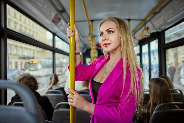 분홍색 옷을 입은 여자는 버스 또는 무궤도 전차 안에 서 있습니다.