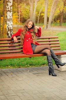 秋の公園に座っている赤いコートを着た女性。