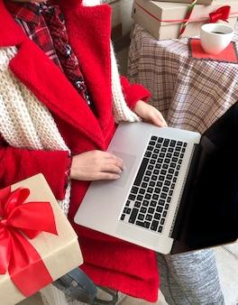 Женщина, одетая в красную шубу с помощью ноутбука накануне праздников рождества и нового года.