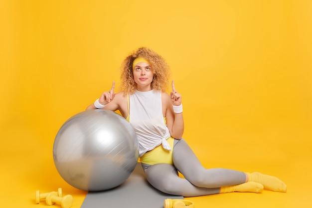 Женщина, одетая в спортивную одежду, указывает выше, с указательными пальцами опирается на фитнес-мяч, демонстрирует место для вашей рекламы на желтом