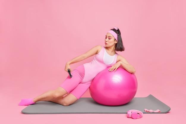 スポーツ服を着た女性は、フィットネスボールに寄りかかってマッサージャーを使用し、ピンクで隔離された自宅でスポーツトレーニングをしています