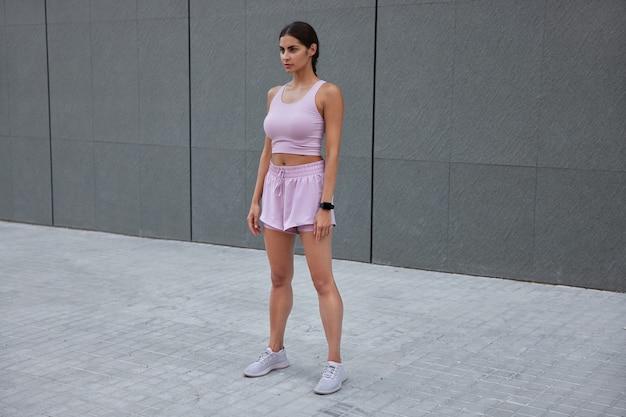 운동복을 입은 여성은 회색 벽에 대고 피트니스 훈련 포즈를 취하고 있습니다. 스마트워치는 야외에서 운동을 기대합니다