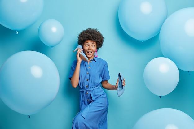세련된 드레스를 입은 여자는 귀 근처에 신발을 보유하고 누군가가 파란색으로 포즈를 취합니다.