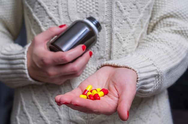 Женщина, одетая в зимнюю одежду с таблетками лекарств. таблетки в руке женщина с легким лечением гриппа. высокая температура.