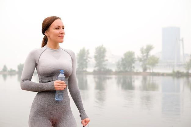 스포츠 훈련 후 레깅스와 최고 음료수를 입은 여성