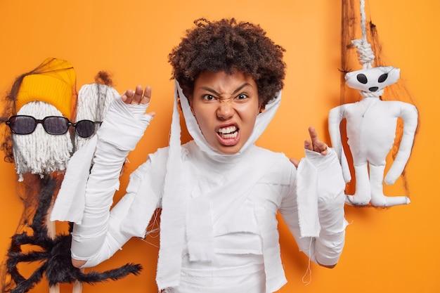 미라처럼 옷을 입은 여성이 이빨을 움켜쥐고 팔을 들고 오렌지에 고립된 휴일 장식에서 할로윈 포즈를 취한다.