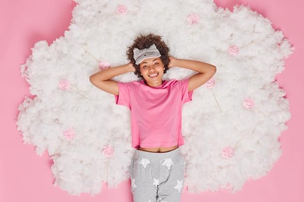 Donna vestita in pigiama tiene le mani dietro la testa sorride gioiosamente si sente rinfrescata dopo aver visto sogni piacevoli e pose dormienti su nuvola bianca