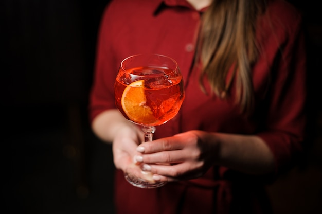 Woman dressed in a red shirt with a tasty aperol syringe summer cocktail