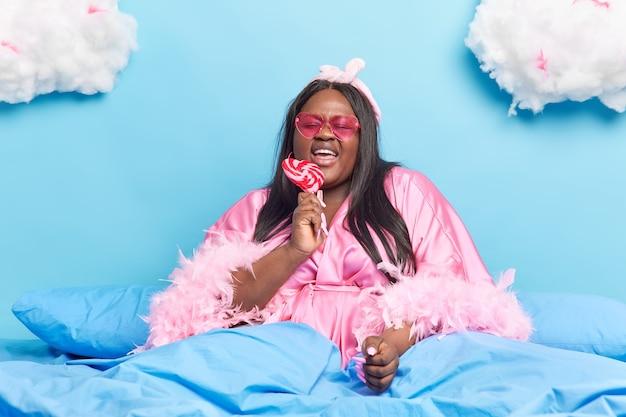 Donna vestita con abito di seta lecca dolci e deliziose caramelle si diverte in un letto accogliente si infila occhiali da sole rosa alla moda ama lo zucchero non si tiene a dieta gode di una giornata pigra a casa