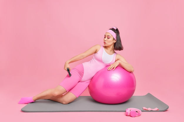 Woman dressed in sportsclothes uses massager leans on fitness ball has sport training at home isolated on pink