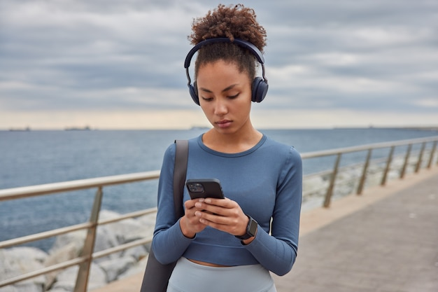 Woman dressed in spotswear checks music from playlist holds mobile phone listens audio track in headphones carries karemat strolls along sea against cloudless blue sky