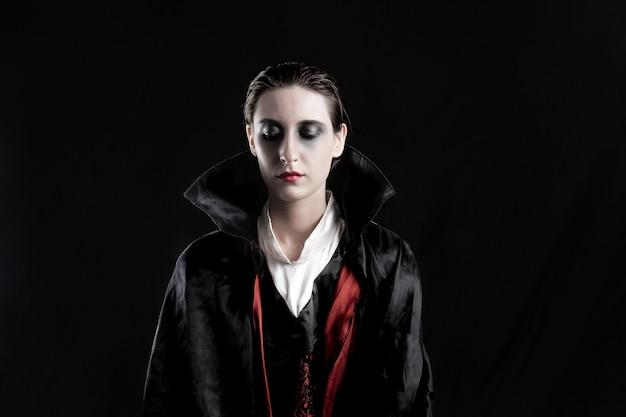 여자는 할로윈 뱀파이어로 옷을 입고. 검은 배경에 드라큘라 의상을 입은 젊은 여성의 극적인 불빛에 스튜디오 촬영