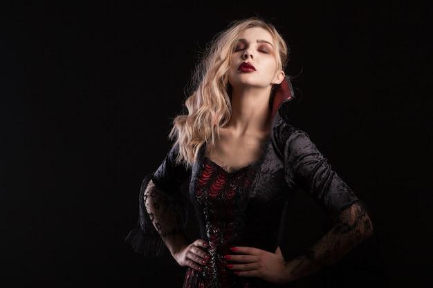 暗い背景でハロウィーンのカーニバルのポーズをとる吸血鬼のような格好をした女性。ハロウィーンのための暗い衣装を着た魅力的な女性。