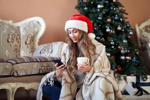 スマートポーンとコーヒーのカップとクリスマスツリーの近くの床に白いセーターのサンタの帽子を着た女性