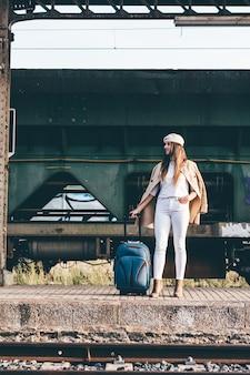 베레모와 베이지 색 재킷을 입은 여성이 오래된 기차역에서 기차를 기다리고 있습니다.