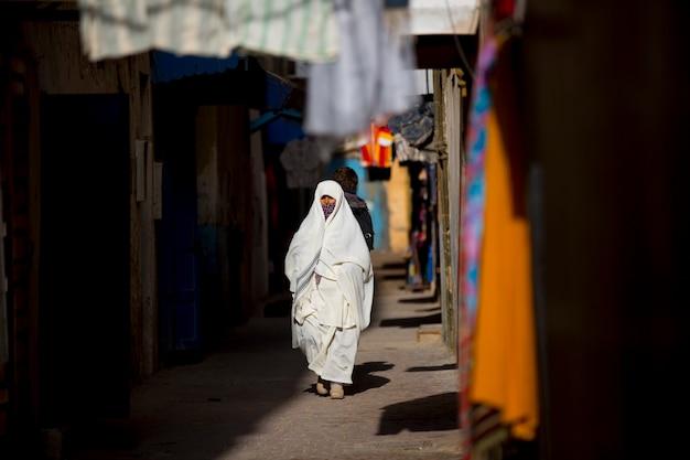 モロッコの市場で買い物をするジュラバを着た女性