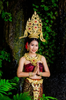 A woman dressed with an ancient thai dress at the waterfall.
