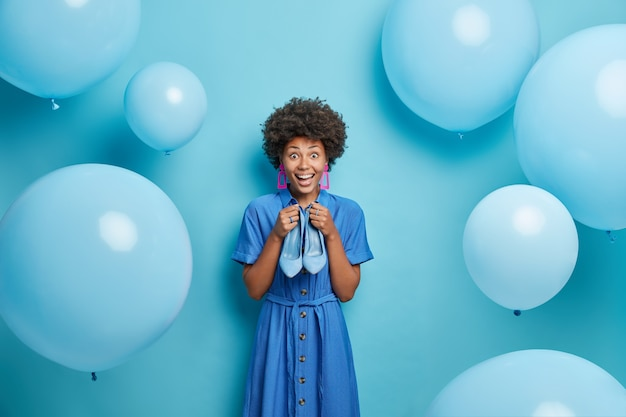 Woman dresses for special occasion wears dress holds high heeled shoes has happy expression poses around inflated balloons isolated on blue