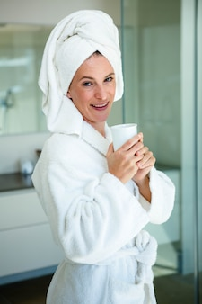 Woman in a dressing gown drinking a cup of coffee