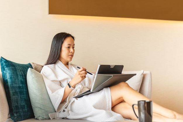Woman in dressing gown sit on couch in hotel room working on laptop.