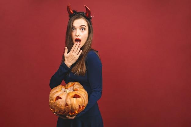 テーマにしたパーティーのための魔女のカチューシャ付きの黒い悪魔のハロウィーンの衣装を着た女性。彼女は「トリックオアトリート」のためにカボチャを保持しています