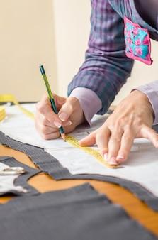 テーブルの上のスーツの鉛筆でテーラーパターンを描く女性の洋裁