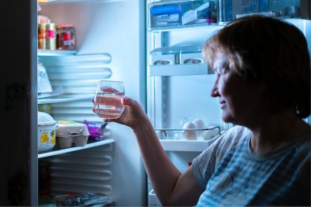 真夜中に冷蔵庫から水を飲む女性b