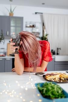 パーティーの後、キッチンでワインを飲む女性