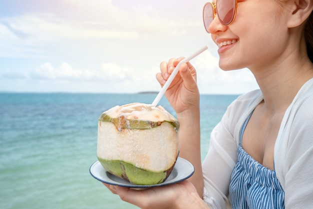 Woman drink a coconut water on comfortable chair on the beach