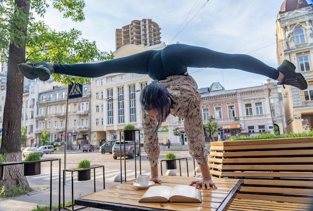 Женщина пьет кофе и читает книгу в кафе на открытом воздухе, концепция образования, обучения и знаний