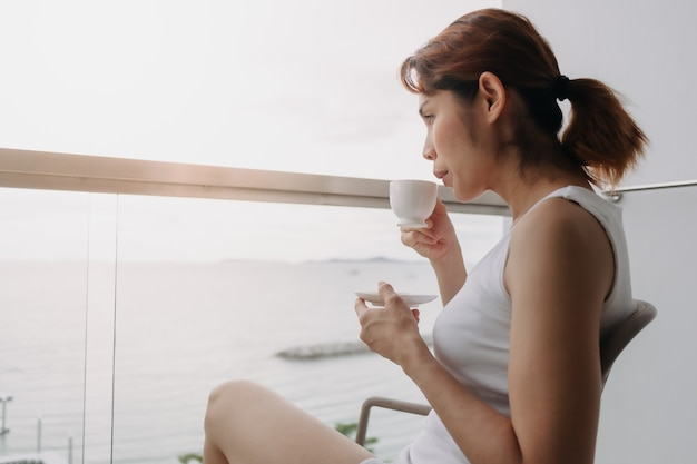 여자는 바다가 보이는 발코니에서 커피를 마시고 휴식을 취합니다.