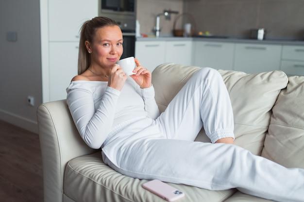 여자 음료 커피 집 흰색 정장에서 소파에 누워 웰빙 나 시간 개념 휴식