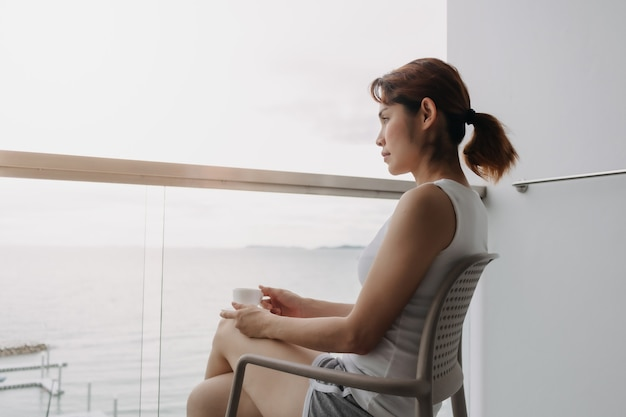 Woman drink coffee and relax on the balcony with sea view