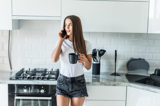 Caffè della bevanda della donna che parla sul telefono cellulare mentre utilizzando computer portatile nella cucina a casa
