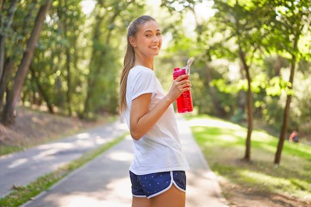 Женщина пьет воду из красной бутылки после утренней тренировки