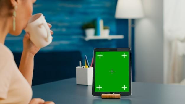 사무실 테이블에 앉아 있는 모의 녹색 화면 크로마 키가 있는 태블릿 컴퓨터를 보면서 커피 한 잔을 마시는 여성. 인터넷 통신 프로젝트를 위해 격리된 가제트와 함께 사용하는 프리랜서