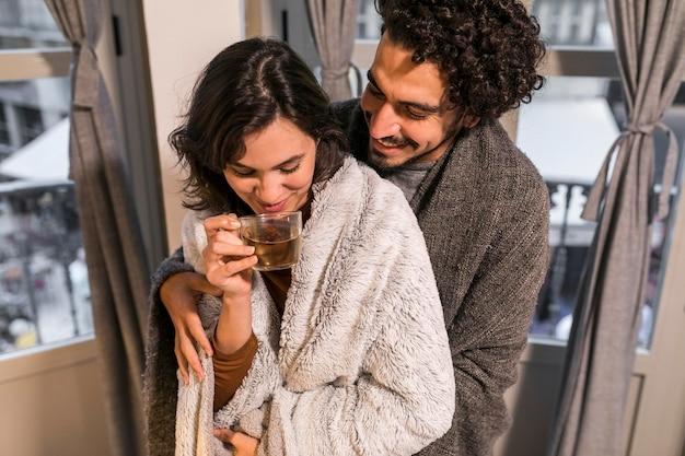 夫の隣でお茶を飲む女性