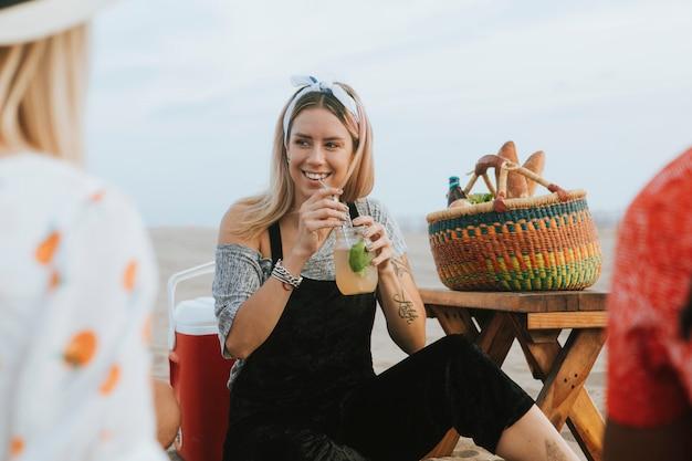 Женщина пьет мохито на пляжной вечеринке