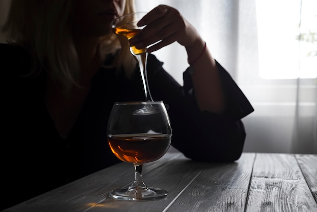 Woman drinking alcohol alone looking out her window.