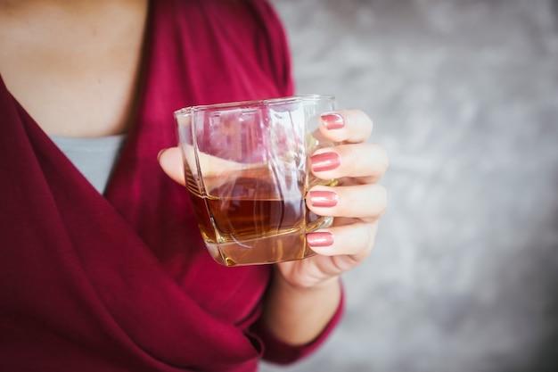 알코올을 마시는 여자, 위스키 유리 근접 촬영을 들고 여자 손