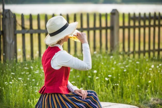 Woman drinking beer on a bench. ligo folk.