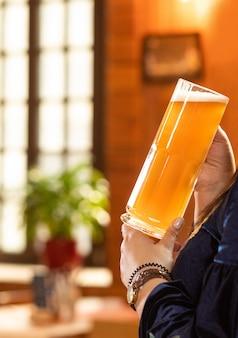 ビールを飲み、レストランでマグカップを保持している女性