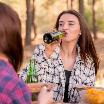 Donna che beve birra mentre all'aperto con gli amici
